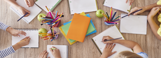 An overhead view of school books, pens and hands