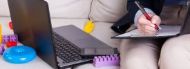 A woman sat on a sofa with a laptop, surrounded by childrens toys